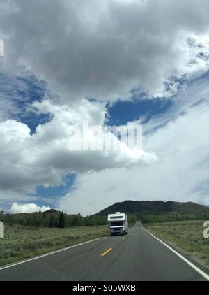 RV driving on high mountain road with big sky - Stock Photo