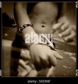 Praying mantis on a six year old boy's hand. Stanislaus county, California, USA - Stock Photo
