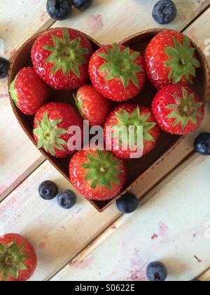 Fresh strawberries in love hearth shape basket and blueberries on vintage table in retro style background - Stock Photo