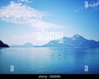 Stand up paddle boarders on Howe Sound, British Columbia with mountain background. - Stock Photo