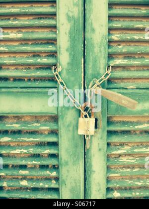 Padlocked louvre green doors - Stock Photo