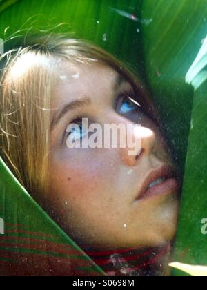Vertical Young woman's face looking upwards wrapped in a green banana leaf matching her eyes. - Stock Photo