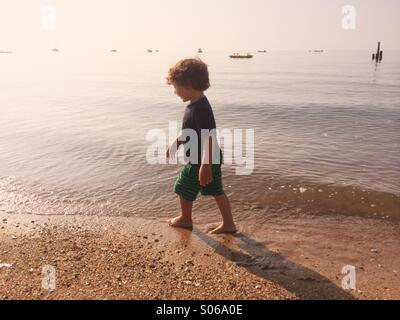 A little boy playing on a sunny beach during summer in Connecticut, USA. - Stock Photo