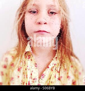 Portrait of a young girl behind a wet window. - Stock Photo
