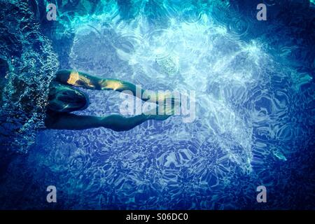 Woman swimming in pool, under water. - Stock Photo