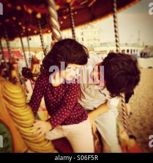 Brother and sister having fun on a merry-go-round / carousel in Brighton, England - Stock Photo