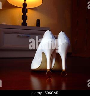Bride shoes on weddin rings - Stock Photo