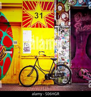 A bike leaning against a wall with graffiti on it. Amsterdam the Netherlands. Europe. - Stock Photo