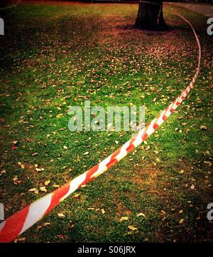 Red and white market tape blowing in wind Stock Photo