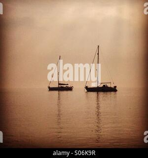 Yachts moored on misty estuary - Stock Photo