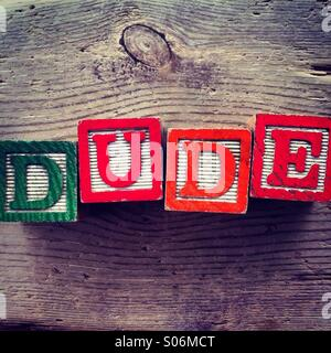 It's a photo of woodblocks toys will alphabet letter on them which are combines together to create the word DUDE - Stock Photo