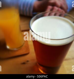 Woman resting arms on pub table that has glasses containing beer and orange juice on it - Stock Photo