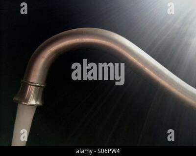 Faucet in kitchen pouring water - Stock Photo