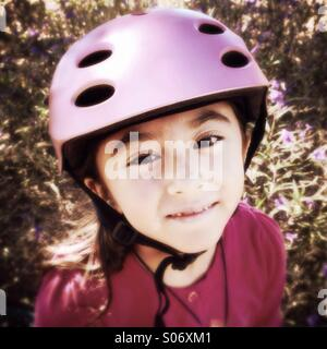 A portrait of a seven-year-old Asian American girl wearing a bicycle helmet looking at the camera. - Stock Photo