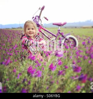 Young girl in flowery field - Stock Photo