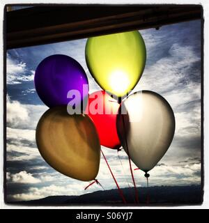 Brightly coloured balloons in front of the sun outside a window against a blue sky with white fluffy clouds. - Stock Photo