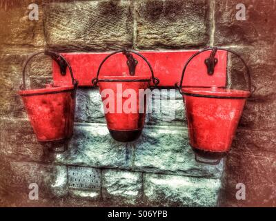 3 red sand and water buckets hanging from brackets on a wall - Stock Photo