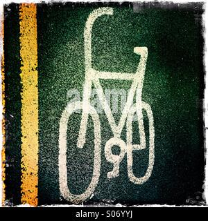 Yellow lines and cycle sign on road - Stock Photo