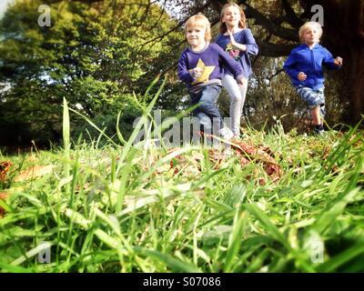 Children running across a Field - Stock Photo