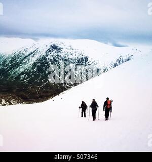 Three mountaineers descend a mountain in Glencoe Scotland - Stock Photo