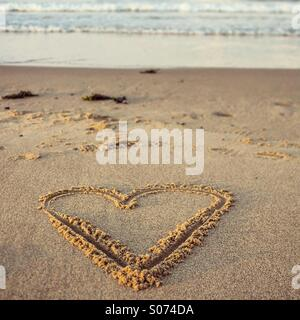 Heart shape drawn in sand on the beach - Stock Photo