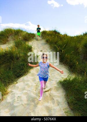 Two five year old children playing in sand dunes - Stock Photo