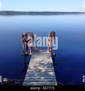 Grandfather and granddaughter go swimming in a Nordic lake together - Stock Photo