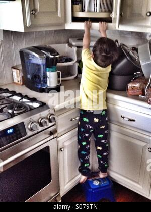 I can get it! Little boy standing on a stool stretching and reaching into a cabinets open door. HDR - Stock Photo