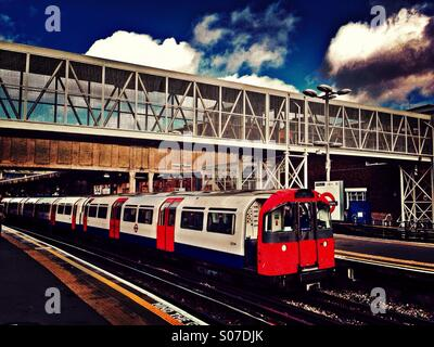 Tube train arriving at Acton Town underground station, London, UK - Stock Photo