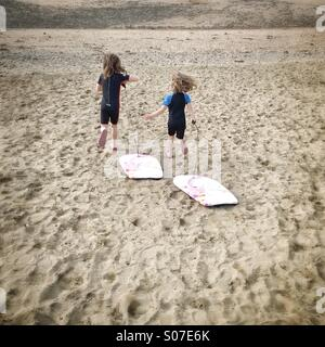 Young children in wetsuits and with body boards running across the sand to go surfing. - Stock Photo
