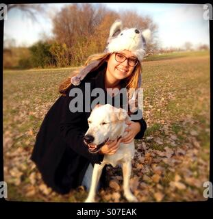 A teenage girl hugging a happy dog. - Stock Photo