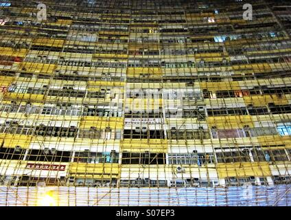 Bamboo scaffolding on a big building in Hong Kong - Stock Photo