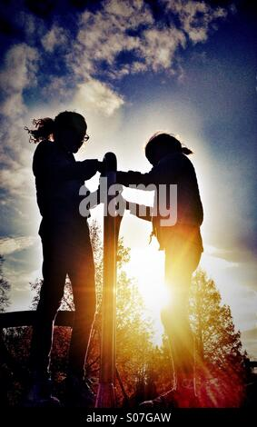 Two young girls playing on modern mini roundabout in silhouette against late afternoon sun - Stock Photo