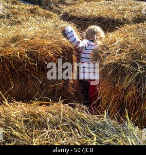 A young girl playing hide and seek in between hay bales at a traditional nordic harvest festival - Stock Photo