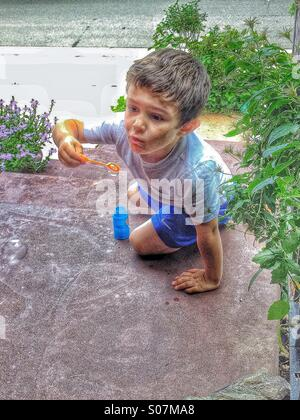 4 year old boy blowing bubbles on porch steps. HDR - Stock Photo