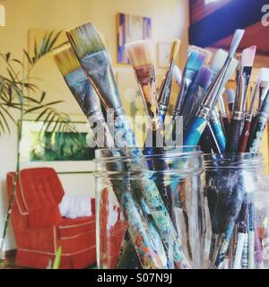 Close up of artist's paintbrushes in jars with artsy bohemian vintage background. - Stock Photo