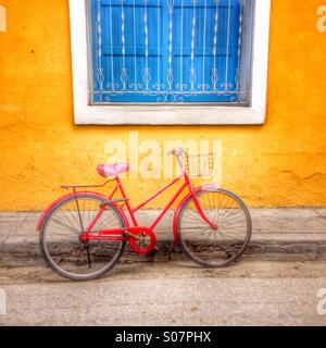 Pictorial image of red painted bicycle set against yellow painted wall with blue painted shuttered window. Trinidad - Stock Photo