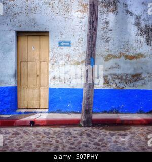 Yellow painted wooden door arrow  direction sign and telegraph pole, Cuba. - Stock Photo