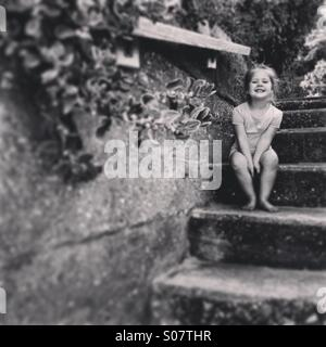 Young girl sitting on stairs - Stock Photo