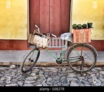 Fruit seller's bicycle with fruit produce lined up on a box at rear of bike. Stood in cobbled street in front of - Stock Photo