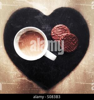 A cup of tea wit two chocolate biscuits sitting on a slate love heart. - Stock Photo