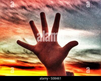 Child's hand against sunset - Stock Photo