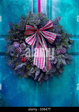 Christmas time - a Christmas wreath on a frosty door - Stock Photo