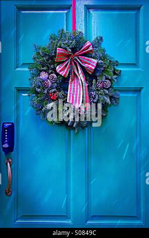 Unlock Christmas - a Christmas wreath hanging on a blue door in the snow - Stock Photo