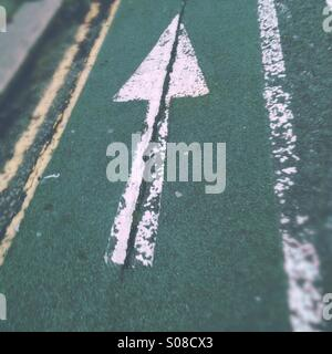 Cycling lane - arrow painted on road - Stock Photo