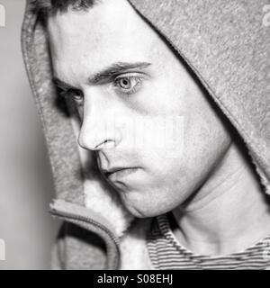 Young male staring away from camera wearing hood - Stock Photo