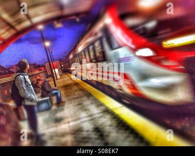 Early morning commuters waiting for train - Stock Photo