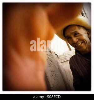 A maya indigenous man exchange a smile as passing by others in San Antonio Palopo, Solola, Guatemala. - Stock Photo