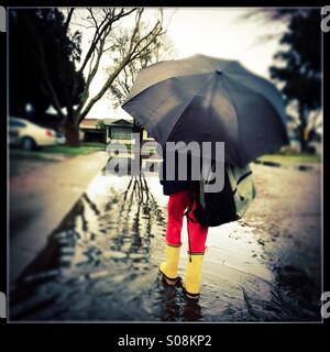 A six year old boy with a school bag holding an umbrella and wearing rain boots walks through a flooded street on - Stock Photo