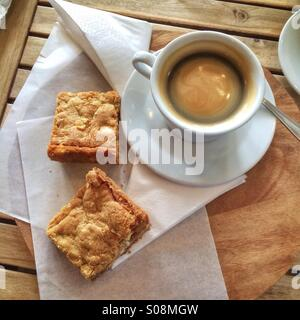 A cup of black coffee and two white chocolate Blondies on a wooden bench in a cafe. - Stock Photo